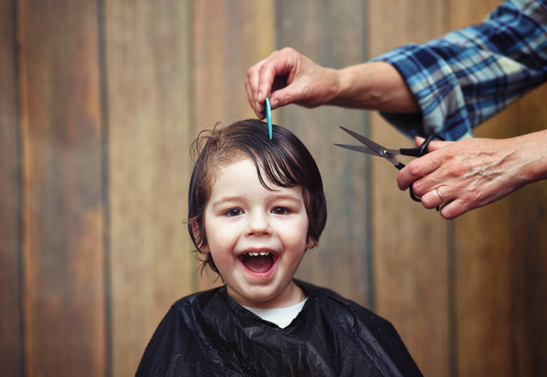 little boy smiling having his hair cut